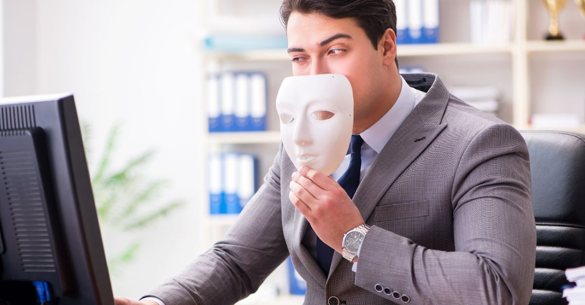 Man holding a mask indicating a possible fraudalent deal