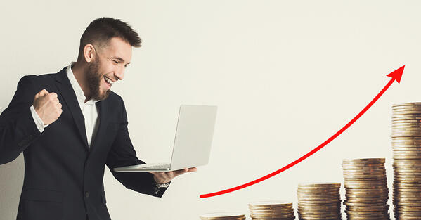 Happy man with a laptop facing increasing stacks of coins and a red arrow on an upward curve