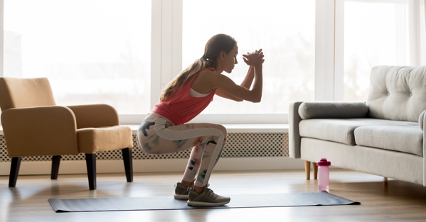Sporty young woman doing squat morning exercise alone in living room