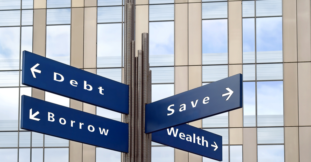 Street signs pointing to different and labelled Debt, Save, Borrow, Wealth