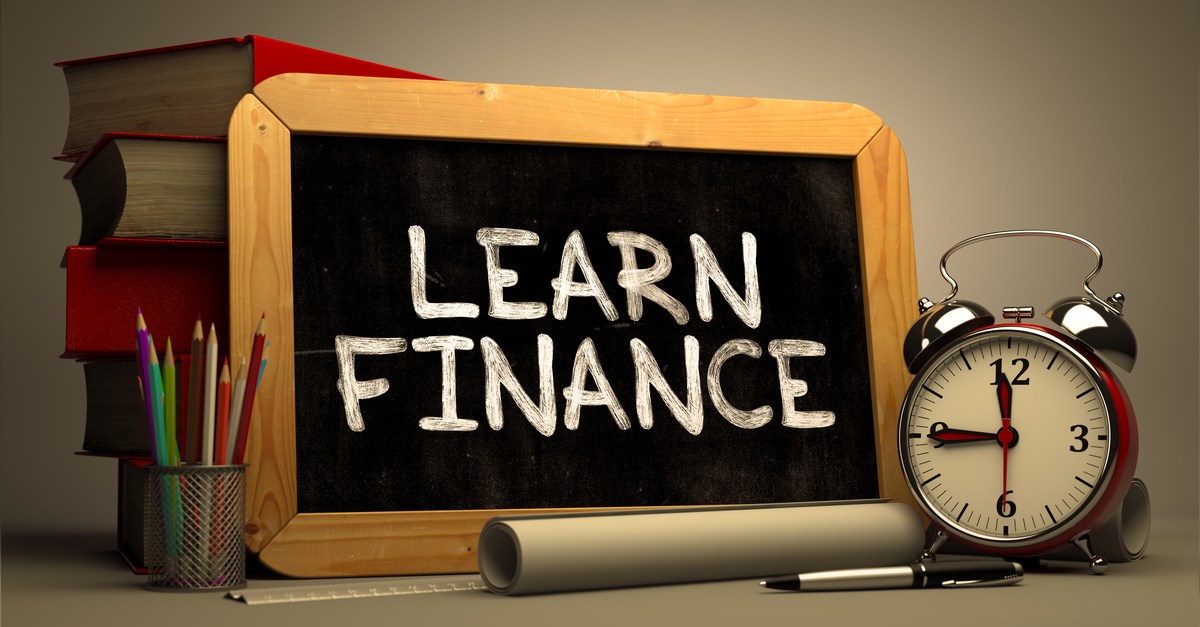 The phrase Learn Finance Handwritten on a Chalkboard, next to a stack of Books, Alarm Clock and Rolls of Paper