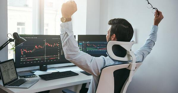 back view of a man with both hand raised in celebration while watching trading charts