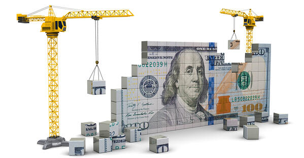concept of building wealth represented by blocks that make up a dollar bill and cranes
