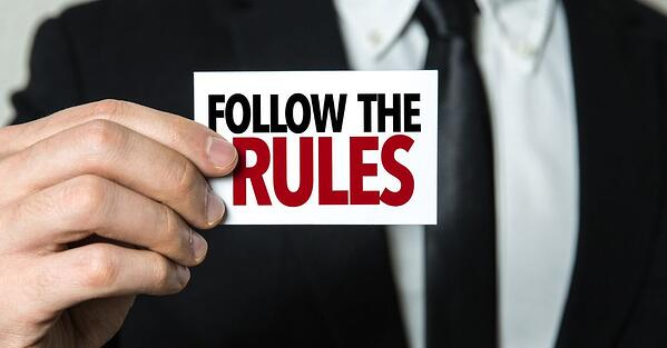 a businessman holding a card that says follow the rules