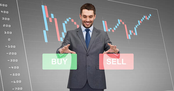 man_standing_over_a_forex_chart_projection_deciding_between_buy_and_sell