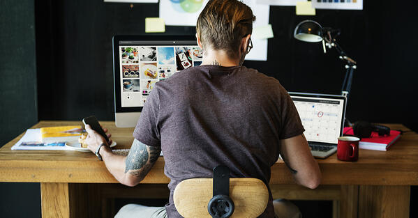 man_working_behind_his_desk_from_home