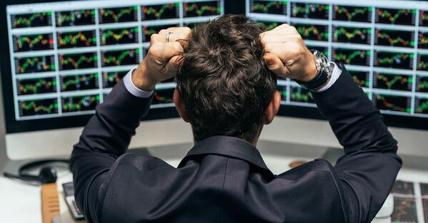 rear view of a stock trader tearing out his hair from despair