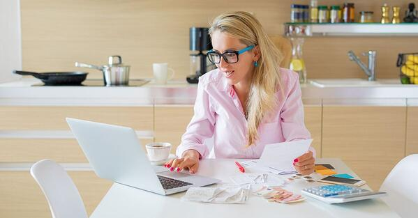 woman organising her finances using a computer, calculator and receipts